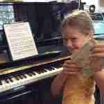 Music Lessons Anywhere piano student Maya with musical envelopes